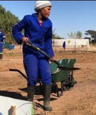 Eine junge Frau der Khoisan Community, die begeistert ihr eigenes Beet bestellt
